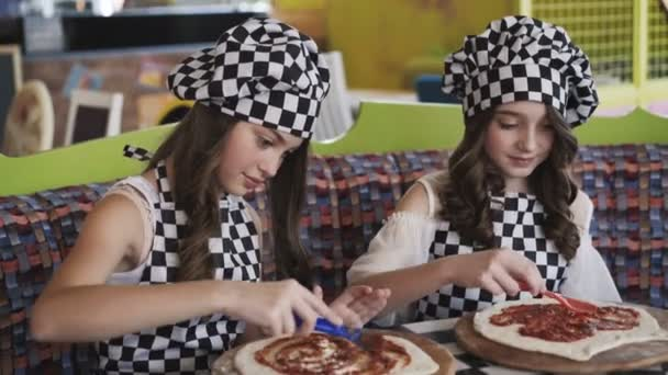 Two cheerful girls in uniform cooking a pizza on master class in cafe 4K