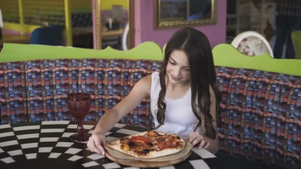 Smiling girl spinning and admiring the pizza presentation in cafe. 4K