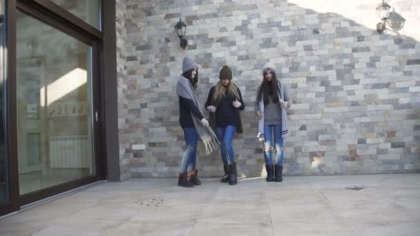 Tři hezké dívky v čepice a svetry baví na dvoře