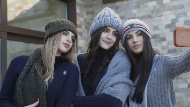 Tři hezké usmívající se dívky do čepice a šála pořizování selfie na dvoře