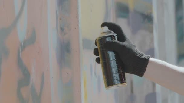 Zavřít pohled na ruku v černé rukavice kreslení graffiti na zdi s balónem