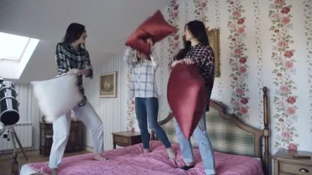 Három fiatal csinos lányok ugrás az ágyon, és szórakozás otthon párna küzdelem