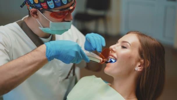 Mladá krásná dívka je v zubní kabinetu na léčbu a zubní čištění. 4k