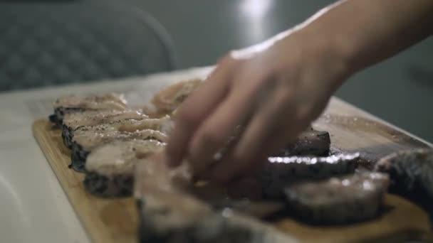 Female hands marinate fish fillet on wooden tablet. 4K