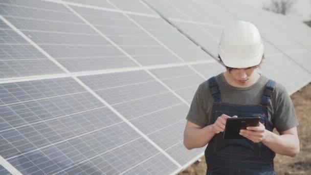 der Ingenieur überprüft die Arbeit der Solarbatterien in der Fabrik mit dem Tablet
