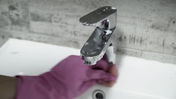 A kéz a kesztyű tisztítása csaptelep a fürdőszobában. Bezárás nézet