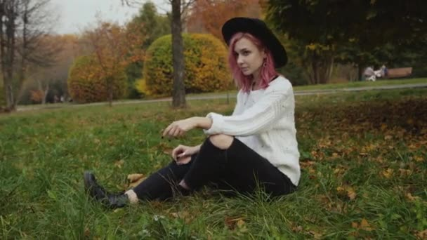 Pretty female hipster rests on the parks lawn and poses at camera