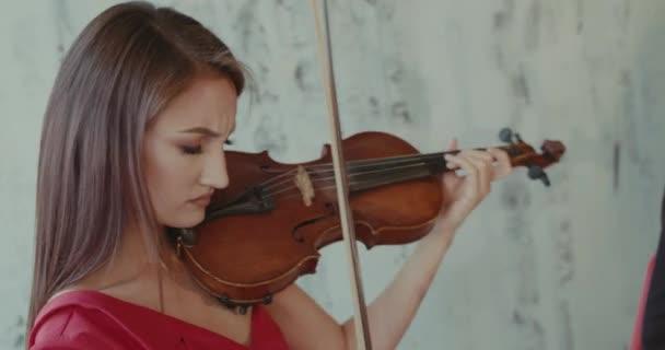 Tekintse meg a csodáló női zenész piros ruhában játszik a hegedűn a kamera
