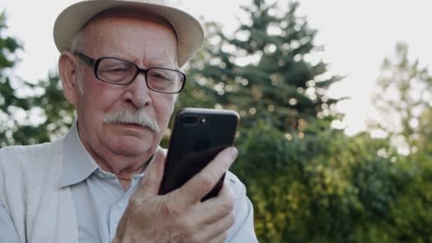 Porträt eines älteren Mannes mit Brille in Hut-Chats auf Handys Web-Kamera im Park