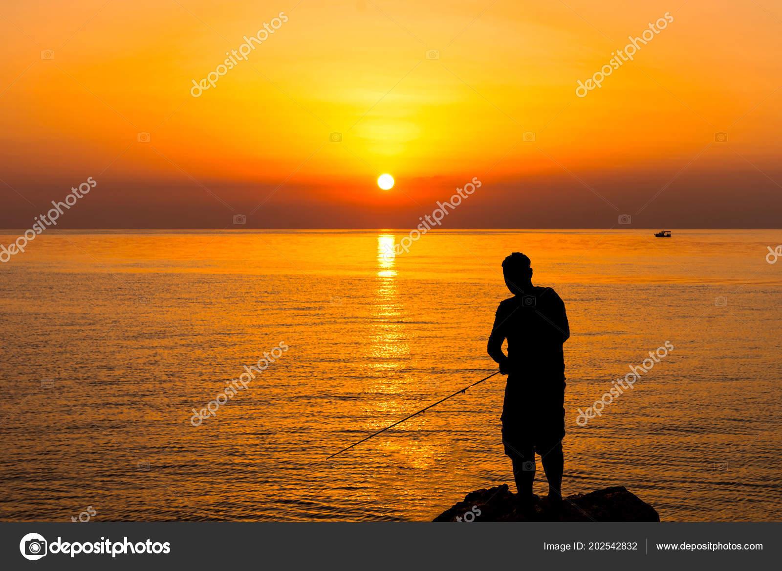Siluetta di un pescatore in riva al mare. Un uomo con una canna da pesca è  in piedi su una pietra vicino all acqua. Pesca all alba. Sole del mattino. 59dbb3b571d7