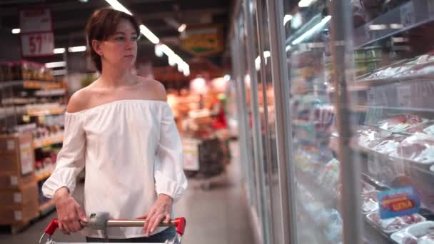 Woman in casual clothes is walking in grocery store steering shopping trolley with food inside it and looking around at shelves with products.