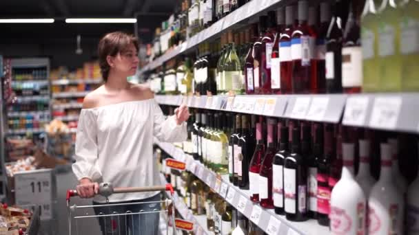 Pretty lady in casual clothes is walking in grocery store steering shopping trolley with food inside it and looking around at shelves with products.
