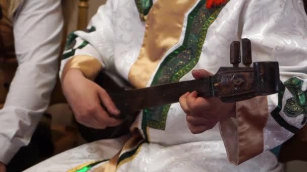 Egy ember, egy régi nemzeti két húros hangszeren játszik. Vértes. Sekély mélység-ból mező