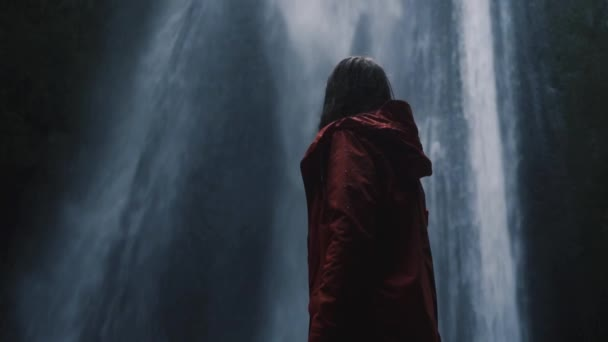 Cinemagraph. Young woman looking at amazing waterfall. Iceland