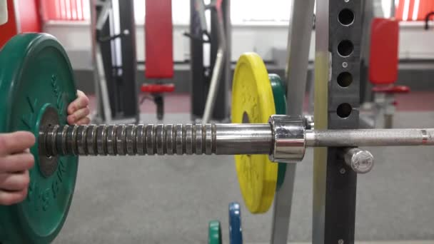 Closeup macro close up of handsome bodybuilder guy prepare to do exercises with barbell in a gym, keep barbell plate in hands, sport man