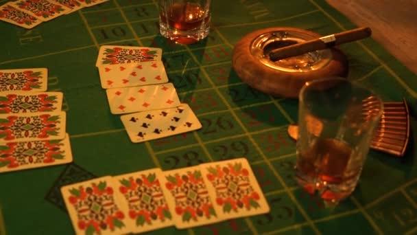Stůl s hrací kartou, whisky, doutníkem a zbraněmi. Kovbojský život.
