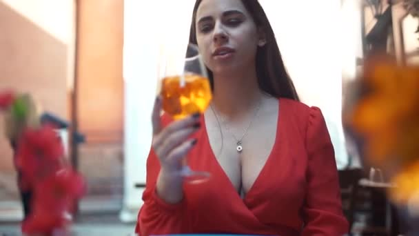 Girl drinks a cocktail spritz aperol in a cold glass in a warm Sunny day in a street cafe