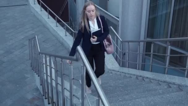 junge Geschäftsfrauen in schwarzer Jacke zu spät und laufen mit Notizbuch in der Hand über die Treppe