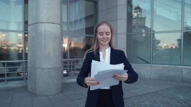 Junge Geschäftsfrauen im schwarzen Anzug betrachten Papierdokumente, lächeln und werfen sie in die Luft. modernes, zeitgenössisches Glasgebäude auf Hintergrund