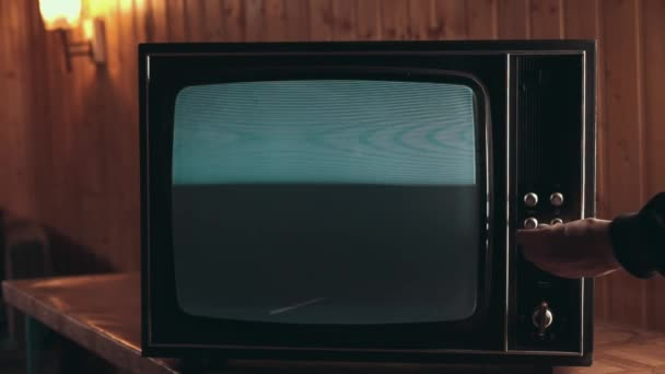 Férfi kézzel megváltoztatja a csatornákat a régi televízió. Az elektromos berendezés interferencia, régi TV-k működnek rosszul. TV-zaj