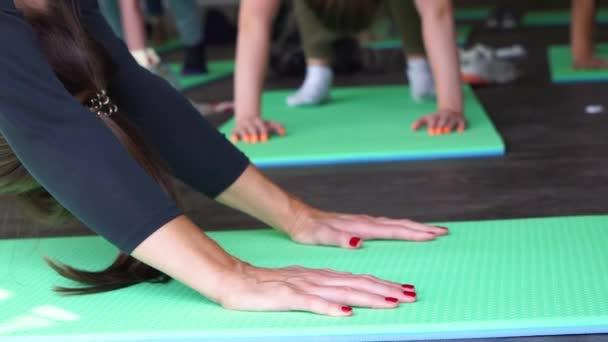 közeli kezek nő jóga osztály nyújtás gyakorlása ülő előre kanyar póz élvezi az egészséges életmód meditáció csoport gyakorlat