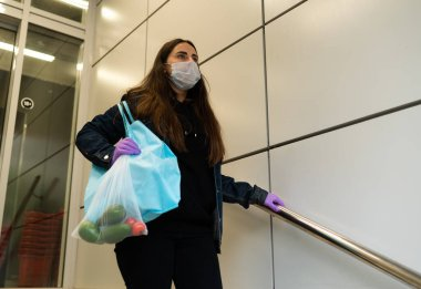 Food delivery young woman in protective mask and gloves carries bag with products from store. Pandemic coronavirus concept