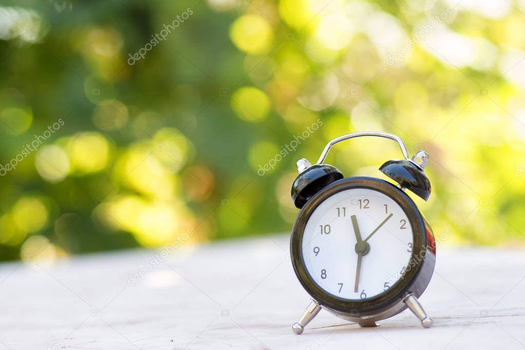 Alarm clock on a light surface on a natural background. Summer concept