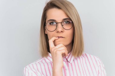 Closeup shot of serious attractive young European woman wearing pink shirt and round glasses keeping finger on her lips, having thoughtful indecisive look, thinking about something important. People stock vector