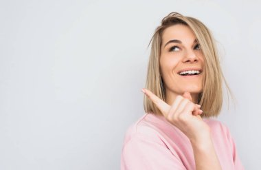 Horizontal portrait of happy blonde hair female wears pink sweater indicates with fore finger aside, demonstrates something at blank copy space for advertisement. People, gesture and emotion concept