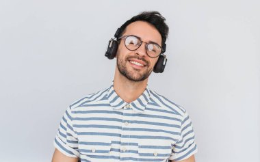 Candid shot of handsome happy young male wearing striped shirt and trendy glasses, with headphones on head, listening favorite music, isolated on white studio background. Copy space for advertising