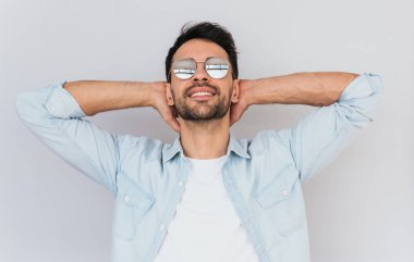 Horizontal portrait of unshaved handsome male model wearing trendy round mirror sunglasses and blue casual shirt posing against white studio background. People, lifestyle and emotions concept