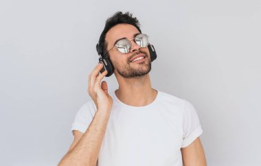 Studio horizontal portrait of happy young male wearing white tshirt and mirros glasses, holding headphones with hand, listening favorite music with closed eyes isolated on white background. Copy space