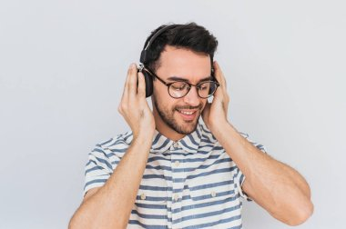 Horizontal shot of handsome happy young male wearing striped shirt and trendy glasses, with headphones on head, listening favorite music, isolated on white studio background.Copy space for advertising