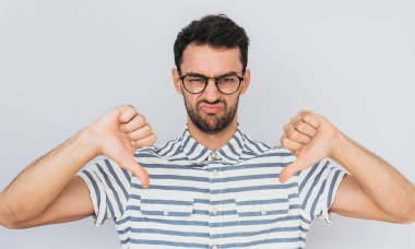 Handsome unhappy male wears round trendy glasses, striped shirt looking at the camera with negative expression, showing thumbs down with both hands. Body language and emotion concept