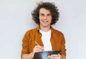 Fotografie Horizontal shot of handsome male student with curly hair, writes in diary plan for next week, wearing white t-shirt and shirt. Busy manager man makes notes in notebook for booking and shipping orders