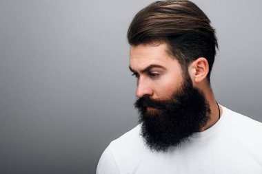 Side view of handsome brutal masculine young bearded male looking aside, posing on a gray studio background. Portrait of young European fashion barber with trendy beard.
