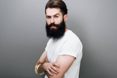 Brutal Caucasian male with thick beard and mustache, dressed in casual white t-shirt posing on gray background. Bearded European man model with confident expression on his face