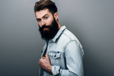 Side view of handsome brutal fashionable young European male with thick beard wearing trendy denim jacket, staring at camera with serious and cheerful look. Barber man posing against gray studio wall.
