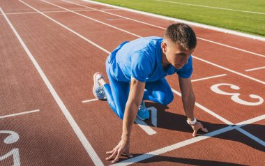 Horizontal shot of young athlete male at starting position ready to start a race. Man sprinter ready for sports exercise on racetrack in stadium. Sport, lifestyle and people concept.
