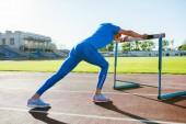 Menschen und Sportkonzept. Sportler turnen bei sonnigem Wetter mit Hindernis auf Laufstrecke. Outdoor-Training von Läufern mit einer Hürde im Stadion.