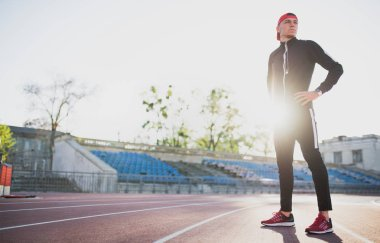 Athletic male posing on the track in the stadium. Attractive runner preparing for running and jogging outdoor. Sport, people and lifestyle concept.
