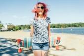 Fényképek Szép fiatal szexi nő, rózsaszín fúj haját, kezében longboard vonzó lövés. Mosolyogva, európai női gyaloglás longboard napos időben. Egészséges életmód. Extrém sportok