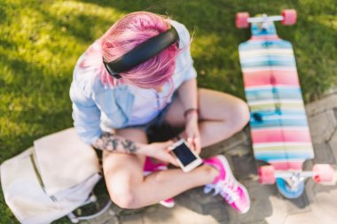 Top view of European beautiful woman with pink hair in headphones listening to music from smartphone sitting in park on green grass background in a blue shirt. Sporty female relaxing after longboarding.