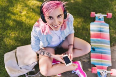 Top view of young smiling beautiful woman with pink hair in headphones listening to music smiling sitting in park on green grass background in a blue shirt. Sporty female relaxing after skateboarding.