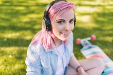 Close up portrait of trendy hipster Caucasian beautiful young woman with pink hair in headphones listening to music from smart phone sitting in park on green grass background in a blue shirt.