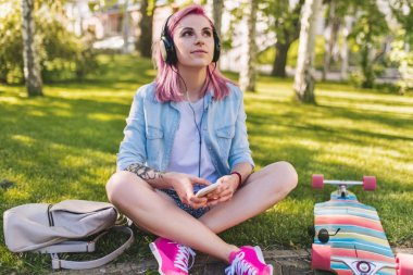 Cute young beautiful woman with pink hair in headphones listening to music dreaming and looking up sitting in park on green grass background in a blue shirt. Sporty female relaxing after skateboarding