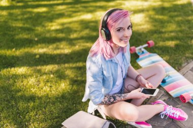 Trendy hipster European beautiful woman with pink hair in headphones listening to music from smart phone sitting in park on green grass background in a blue shirt. Female relaxing after skateboarding.