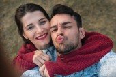 Fotografie Romantic fashion traveling couple making self-portrait on park background. Caucasian handsome man and beautiful woman embracing together at date day, blowing kiss on nature backgroud.Lifestyle concept