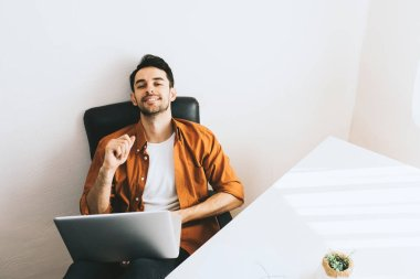 Above shot of happy businessman with cheerful smile achieving life goals. Success and achievement concept. Candid Caucasian businessman sitting with laptop and relax with legs on table, looking up.