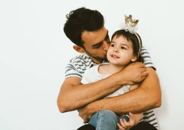 Beautiful shot of cute toddler girl wearing crown, on her birthday, embrace with dad against white background. Portrait of affectionate father kiss and hug his daughter. Happy relationship family.